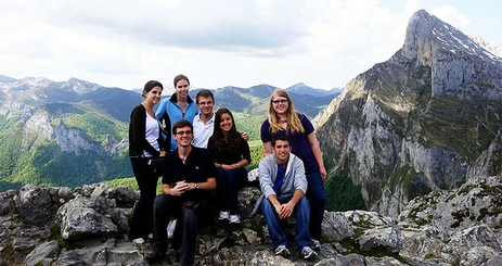 Students sit at the summit of a mountain.